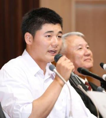 記者会見でプロ志望を表明した早実高の清宮幸太郎選手。右は和泉実監督=22日午後、東京都内