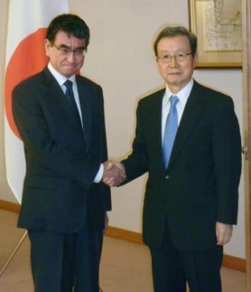 中国の程永華駐日大使(右)と握手する河野外相=25日午後、外務省