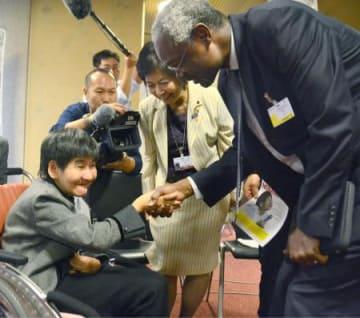 国連環境計画のイブラヒム・ティアウ事務次長(右)と面会する、胎児性水俣病患者の坂本しのぶさん(左)=25日、スイス・ジュネーブ(共同)
