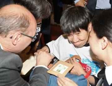 28日、「水俣への思いをささげる時間」でのスピーチを終え、締約国会議の議長(左)と握手を交わす坂本しのぶさん=スイス・ジュネーブ(共同)