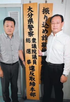 看板を掛ける高山譲二刑事部長(右)と幸野俊行捜査2課長=29日午前、県警本部