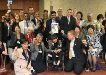 帰国を前に、NGO関係者らと記念写真に納まる坂本しのぶさん(前列左から3人目)=29日、ジュネーブ(共同)