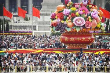 国慶節を迎え、大勢の観光客でにぎわう北京の天安門広場。「喜んで第19回党大会を迎えよう」と書かれた花飾りが置かれた=1日(共同)