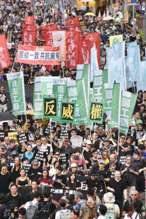 香港中心部で、黒い服を着てデモ行進に参加した市民ら=1日(共同)