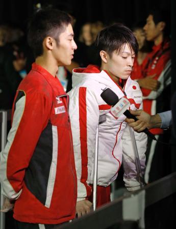 体操の世界選手権男子予選で左足首を痛めて途中棄権し、松葉づえ姿で取材を受ける内村航平。左は白井健三=2日、モントリオール(共同)