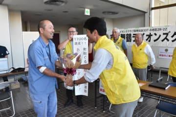 通算1700人目の献血者となり、図師会長(右)から花束を受ける黒木さん