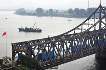 中国遼寧省丹東市(左側)から橋を渡り北朝鮮・新義州に向かうトラック=9月(共同)
