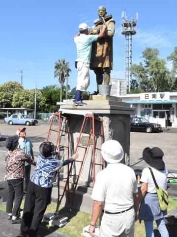 協力してマンショ像を磨き上げる市民たち