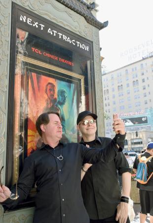 映画「ブレードランナー 2049」のポスター前で、写真を撮るファン=6日、米ハリウッド(共同)