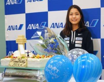 21歳の誕生日を迎え、ジャンプ台を模したケーキを贈られた高梨沙羅=8日、羽田空港