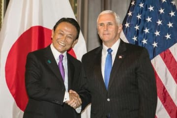 日米経済対話で握手する麻生財務相(左)とペンス米副大統領=16日、ワシントン(代表撮影・共同)
