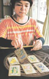 よく交ぜたタロットカードを一枚一枚めくって並べ、未来を占うTOMOさん=仙台市若林区中倉1丁目