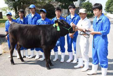 都城農業高畜産科の2年生に囲まれた雌子牛「あさこ」と寄贈した押川さん(右から2人目)
