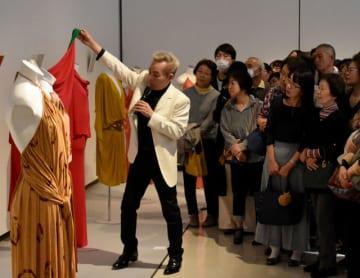 手に取りながらカクテルドレスについて説明する鳥丸軍雪さん=21日午後、宮崎市・みやざきアートセンター