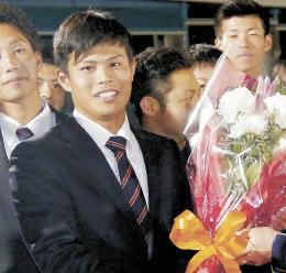 3位指名され、花束を手に笑顔を見せる国学院大の山崎