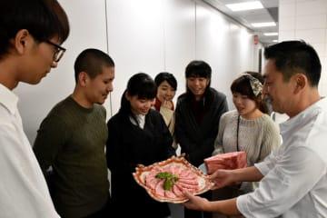 オランダ・アムステルダムの日本料理店で、県産食材のPRイベントを開いた学生たち=27日午後(現地時間)