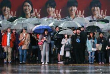 傘を差し、信号待ちをする人たち=29日夕、東京・渋谷
