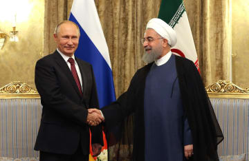 1日、イラン首都テヘランでロウハニ大統領(右)と握手するロシアのプーチン大統領(イラン大統領府提供、ゲッティ=共同)