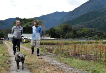 武者小路実篤が暮らした日向新しき村を初めて訪れた孫の知行さん(左)と、案内する松田さん=3日午前、木城町石河内