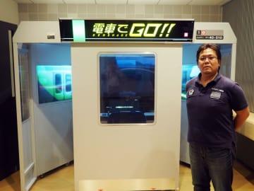 11月7日に稼働開始のタイトーのゲーム機「電車でGO!!」と、開発者の金田剛・制作1課長=10月23日午後、東京都新宿区