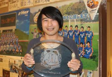 制作したJ1昇格記念盾を手に笑顔を見せる竹田さん=長崎市、居酒屋「はち蔵」