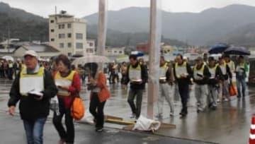 放射性物質が付着していないかを調べるゲート型モニターを通り、大分へ向かうフェリーに乗船する避難者ら=14日午前、愛媛県伊方町の三崎港