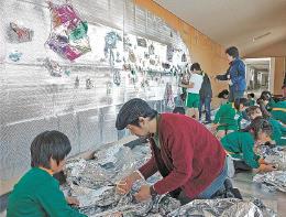 美術家の杉戸さん(中央)と一緒にアルミホイルを使った造形に挑戦する子どもたち