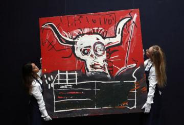 ニューヨークでの競売を前に、米国人画家バスキアの絵画「カブラ」を展示する関係者=10月6日、ロンドン(AP=共同)