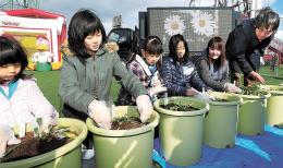 愛梨ちゃんゆかりの花の苗をプランターに植える美香さん(右から2人目)ら参加者たち