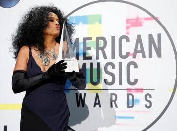 「アメリカン・ミュージック・アワード」の授賞式で生涯功労賞のトロフィーにキスをするダイアナ・ロスさん=19日、ロサンゼルス(ロイター=共同)