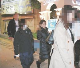 捜査員に連行される従業員の女(中央)=2017年11月21日午前2時55分ごろ、仙台市青葉区国分町2丁目(写真の一部を加工しています)