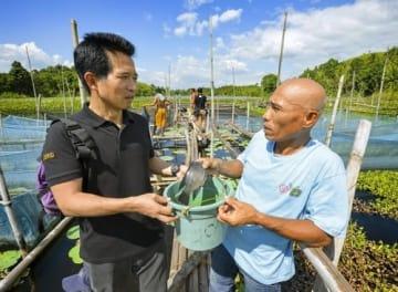 JICAの支援を受けたテラピア養殖場がある村で、住民に養殖の進み具合を尋ねる落合直之さん(左)。住民は「別の場所で稚魚を買って育てていたのが、今では産卵から始められるようになった」と笑顔で答えた=3月、フィリピン南部ミンダナオ島のコタバト市郊外(撮影・村山幸親、共同)