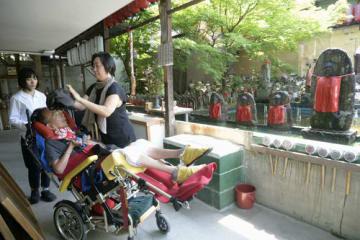 車椅子で散歩中、千本ゑんま堂で、志賀玲子さん(右)に帽子を取ってもらう甲谷匡賛さん。散歩は雨の日も雪の日も欠かさない。「暑い夏が大変。日差しも強いので日焼けしないようにしなきゃね」と志賀さん=5月23日、京都市上京区(撮影・井田公雄)