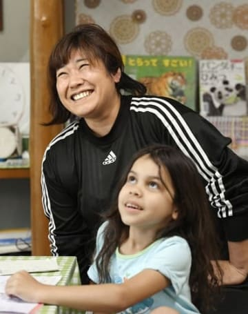 日系ブラジル人の子どものそばで笑う川口祐有子さん。「九番団地では、日本人と外国人の住民の相互理解が進む。学ぶ子どもたちの姿が意識を変えた」と考えている=5月17日、名古屋市港区(撮影・猪狩みづき)