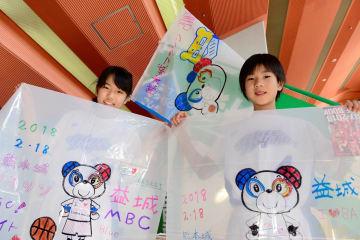 熊本城マラソンの出場ランナーに配る防寒ポンチョにイラストやメッセージを描いた子どもたち=県立総合体育館(池田祐介)