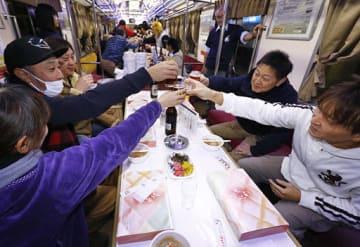 「乾杯!」とグラスを合わせ忘年列車を満喫する乗客たち=8日午後6時28分