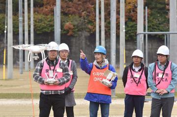 関電の研修用の電柱が立ち並ぶグラウンドで行われた実地講習。初めてコントローラーを持つ人もいたがインストラクターの指導でPhantom 4を使って、目印に置かれたパイロンの上空を飛行させていた=8日、大阪府茨木市の関西電力能力開発センター