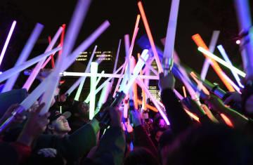 15日、米ロサンゼルスでのイベントで、劇中の武器「ライトセーバー」を手に盛り上がる「スター・ウォーズ」ファン(AP=共同)