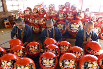 新年用のだるまに名入れする僧侶たち=桜川市本木の雨引観音