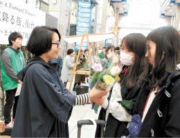 10月29日に初めて開催されたイベントで、3本の花を受け取る来場者=仙台市青葉区の七十七銀行名掛丁支店前