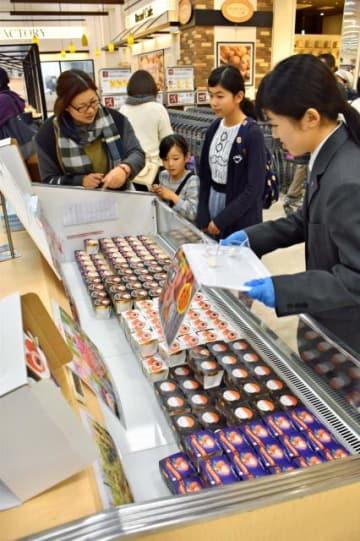 客にライチ入りアイスクリームについて説明する宮崎学園高の生徒=24日午前、宮崎市・イオンモール宮崎