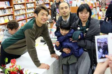 サイン会に訪れたファンと記念写真に納まる梅崎選手(左)=紀伊國屋書店長崎店