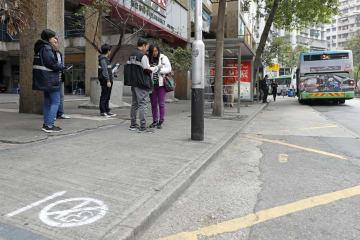 新たに禁煙ゾーンに設定されたバス停の周囲を巡回するSSMの「禁煙Gメン」たち=2018年1月1日(写真:SSM)