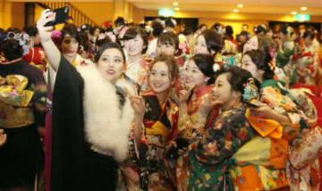 スマートフォンで記念撮影する振り袖姿の新成人たち=5日、豊後高田市玉津の中央公民館
