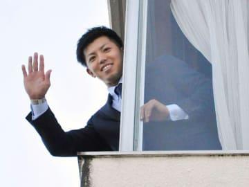 「青星寮」に入寮し、窓から手を振るDeNAの東=7日、神奈川県横須賀市