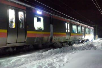 積雪のため動けなくなり、乗客が車内に閉じ込められたままのJR信越線の電車=12日午前1時15分、新潟県三条市