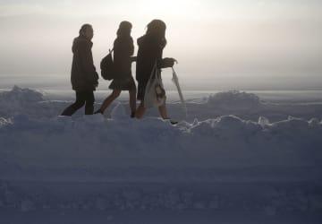 大雪で立ち往生したJR信越線の車両から降り、線路を歩く女性=12日午前、新潟県三条市