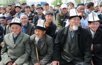 キルギス南部ジャララバードの集会で、伝統的な帽子「カルパク」をかぶる男性たち(手前)=2010年4月(共同)