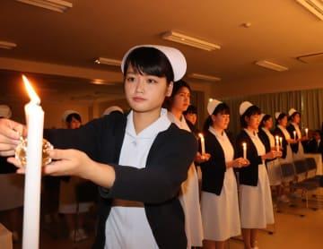 ナースキャップを授かり、ろうそくから灯をともす学生=佐世保市、九州文化学園歯科衛生士学院