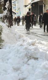 歩道の雪は、通行する人の邪魔にならないよう積み上げられた=23日午前8時40分、仙台市青葉区本町